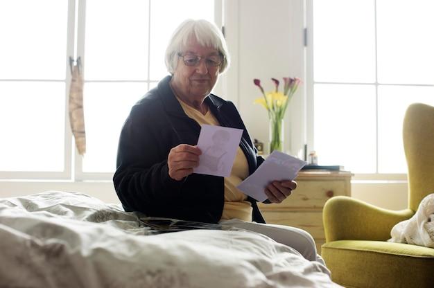 Hogere vrouwenzitting op het bed en het bekijken foto's