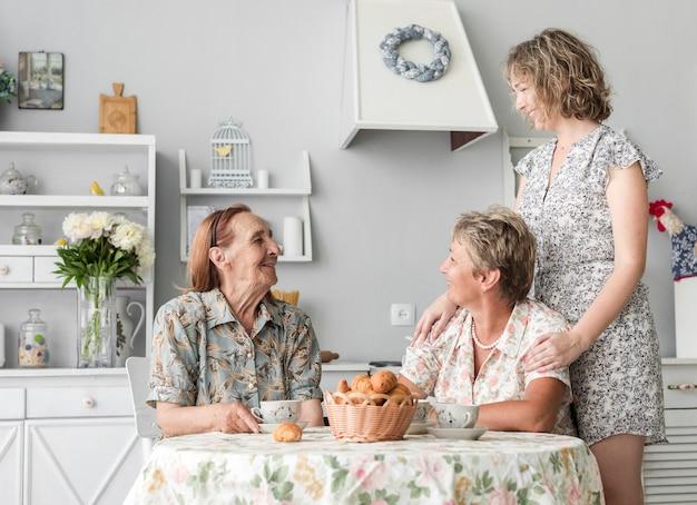Hogere vrouwenzitting op stoel die haar dochter en kleindochter in keuken bekijken