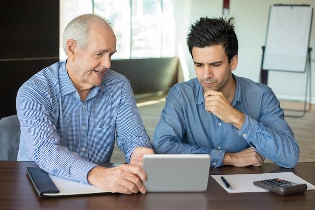 Hogere werkgever die gegevens toont aan jonge werknemer op tablet