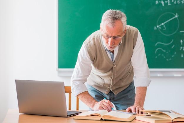 Hogere wiskundeleraar die met pen schrijven terwijl status tegen bord