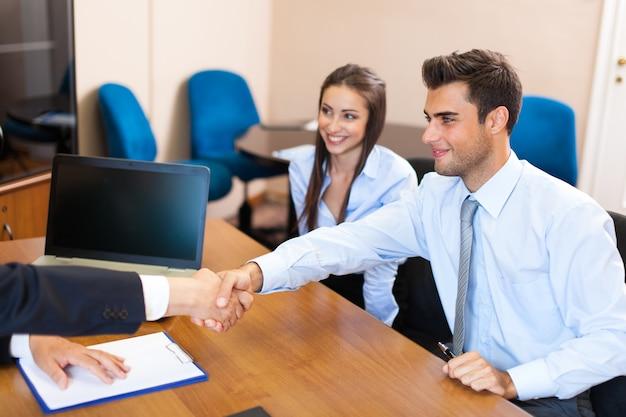Hogere zakenman die een document toont om aan een paar te ondertekenen