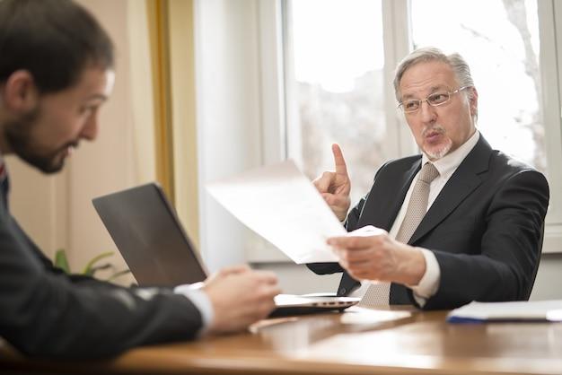 Hogere zakenman die een werknemer berispt