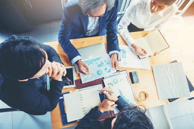 Hogere zakenman die handgebaar gebruiken terwijl businessplan en bespreking in de vergadering verklaren. geselecteerde focus