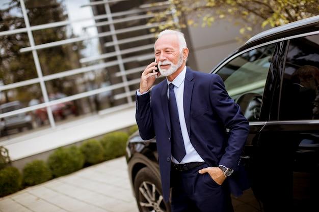 Hogere zakenman die mobiele telefoon met behulp van dichtbij auto