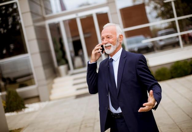 Hogere zakenman die mobiele telefoon voor de bureaubouw met behulp van