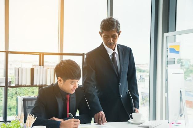 Hogere zakenman die ondergeschikte zakenman over het werk onderwijst.