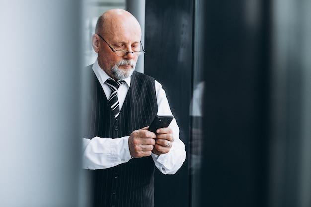 Hogere zakenman die op de telefoon op het kantoor spreekt
