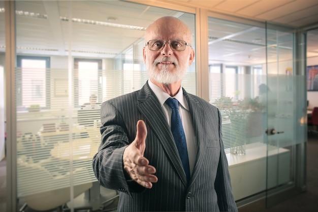 Hogere zakenman die zijn hand aanbiedt