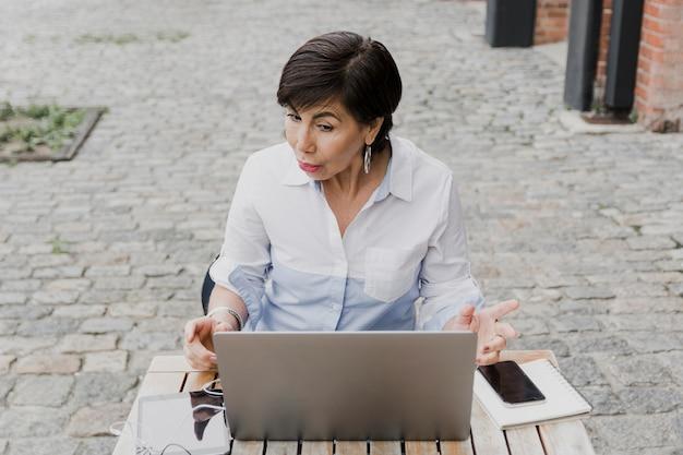 Hogere zitting in openlucht met het laptop middelgrote schot