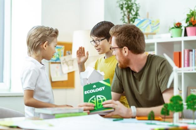 Holding gepresenteerde modellen. jonge actieve leerlingen bespreken het onderwerp van hun les terwijl de leraar aandachtig naar hen luistert