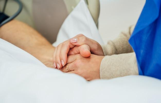 Holding patiënt handen in een ziekenhuis. familie hulp. detailopname. ondersteuning.