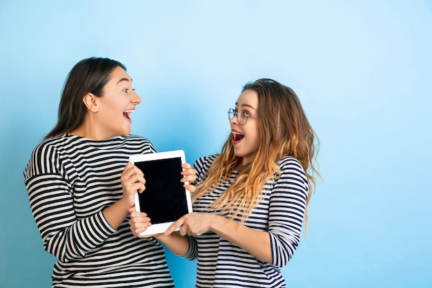 Holding tablet met leeg scherm. jonge emotionele vrouwen geïsoleerd op gradiënt blauwe studio achtergrond. concept van menselijke emoties, gezichtsuitdrukking, vriendschap, advertentie. mooie modellen in vrijetijdskleding.