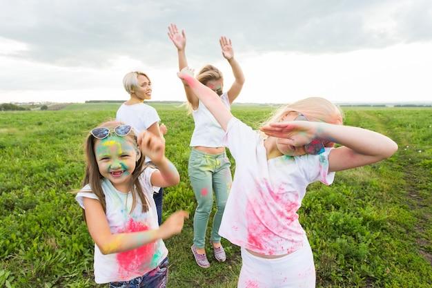Holi-festival, vakantie en geluksconcept - jonge tieners en vrouwen in kleuren hebben plezier buiten