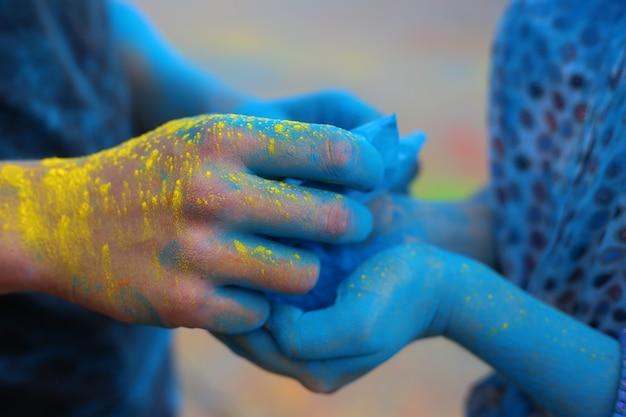Holi festival van kleuren. handen die holiverf dicht tegenhouden.