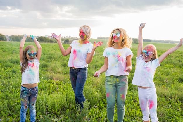 Holi festival, vriendschap, vakantie en mensen concept - gelukkige vrouwen en meisjes springen bedekt met verf