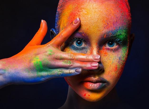 Holi kleurenfestival. portret van schoonheid model met kleurrijke poeder make-up poseren. mooie vrouw met regenboogmake-up. abstracte kleurrijke kunstsamenstelling, bijsnijden