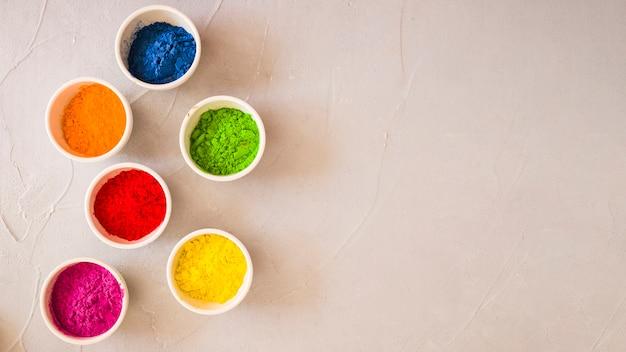 Holi-kleurenpoeder in witte kom op geschilderde geweven achtergrond
