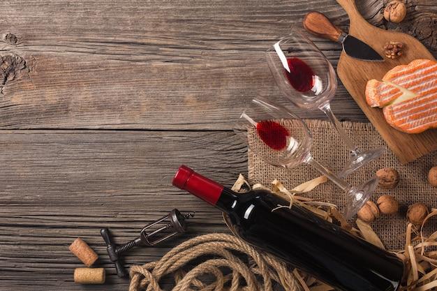 Holiday dinner setting met rode wijn en afromende kaas op rustieke hout. bovenaanzicht met ruimte voor uw groeten.
