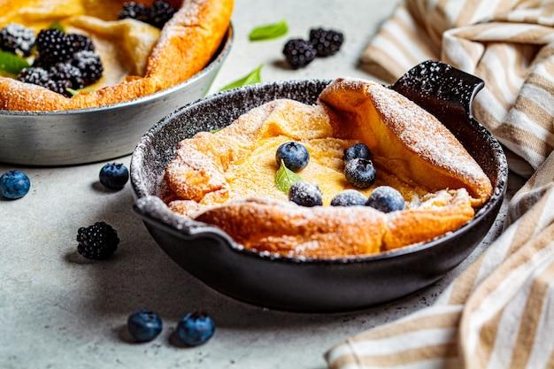 Hollandse baby pannenkoek met bessen en citroen in gietijzeren koekenpan.
