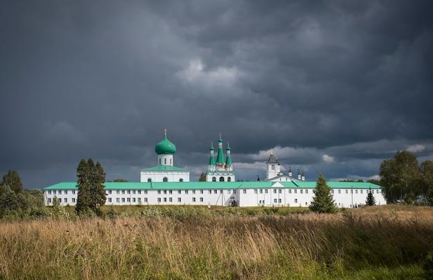 Holy trinity alexander svirsky-klooster aan het roshinskoye-meer in de regio leningrad, rusland. tegen de achtergrond van een stormachtige lucht, op een zomerse dag