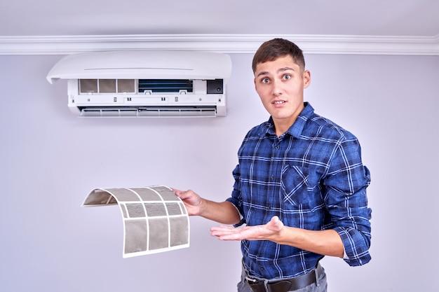 Home airconditioner vervangen en schoonmaken concept. geschokt gezicht professionele fixer toont vuile filters