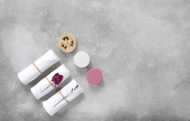 Home beauty essentials & zelfzorg. grijze achtergrond, crème, masker, handdoeken. plat liggen. kopieer ruimte.