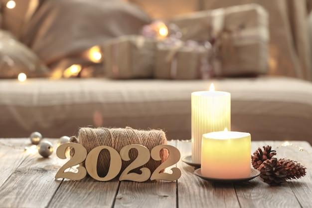 Home christmas-compositie met decoratieve houten 2022-nummers, kaarsen en decordetails op een wazige kamerinterieurachtergrond.