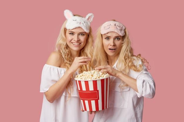 Home cinema online. jonge vrouwen in pyjama en slaapmaskers kijken naar een film thuis op isolatie voor een televisie met popcorn