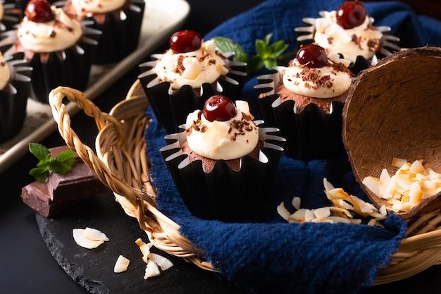 Home cooking concept zelfgemaakte zwarte woud kokosroom cupcakes op blauw servet met kopie ruimte