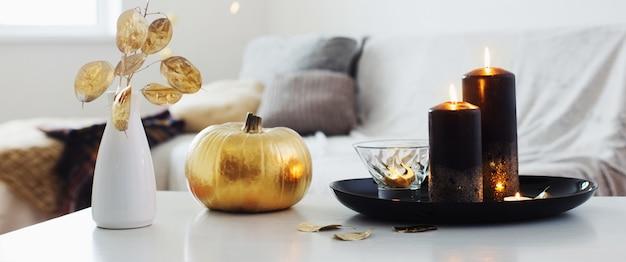 Home decor met gouden pompoen en brandende kaarsen