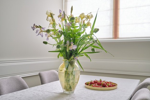 Home eetkamer interieur, lente zomer boeket bloemen, aardbeien