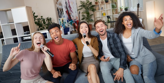 Home entertainment groep jonge gelukkige multiculturele vrienden die karaoke spelen thuis zingend met
