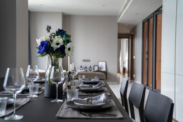Home inerior met eettafel setting met bloem, zwart roestvrij bestek en keramisch servies op nartual houten blad / interieur