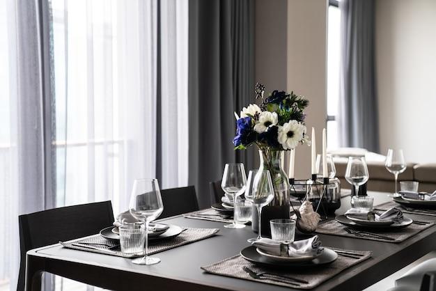 Home inerior met eettafel setting met gouden roestvrijstalen servies zwart bestek setting op nartual marmeren blad / interieur