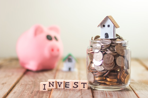 Home-investering, geld te besparen voor hypotheek, munten in een glazen pot op houten tafel