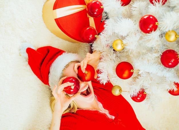 Home kerstsfeer. schoonheid model meisje in kerstmuts op huis ontwerp versieren. holly jolly swag christmas and noel. grappig. emoties.