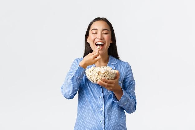Home leisure, logeerpartij en slaapfeestje concept. glimlachend opgetogen aziatisch meisje dat geniet van het eten van favoriete popcorn, het dragen van een pyjama in het weekend, het kijken naar favoriete film, witte achtergrond