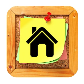 Home-pictogram op gele sticker op prikbord van kurk.