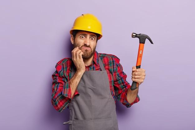 Home renovatie concept. verontwaardigde bouwer houdt hamer vast, repareert