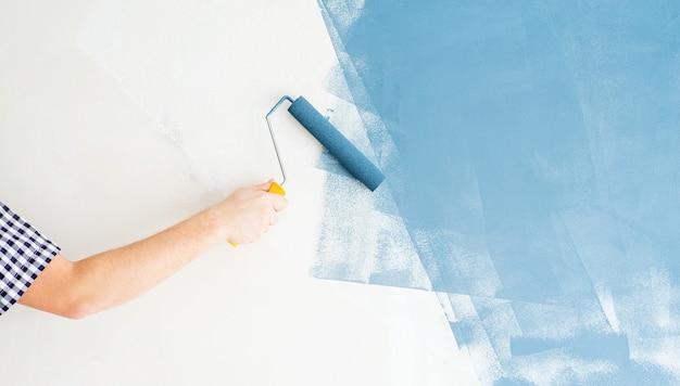 Home reparatie en verbetering. man kleurende muur blauw met een roller