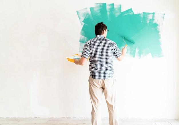 Home reparatie en verbetering. man kleurende muur groen met een roller