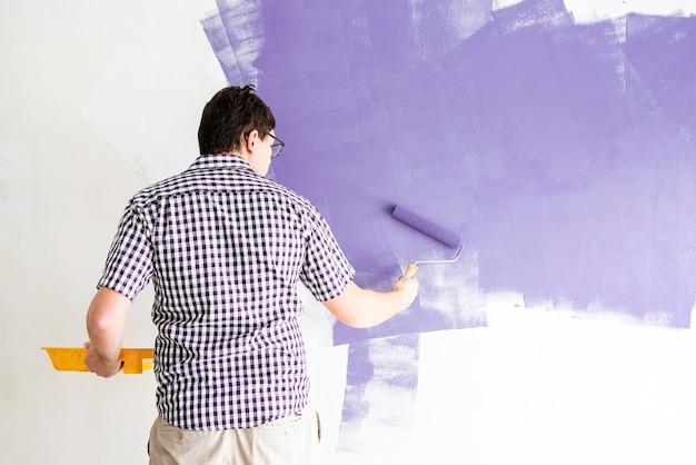 Home reparatie en verbetering. man kleurende muur paars met een roller
