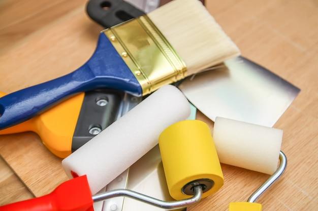 Home reparatie tools op houten achtergrond. schuim- en rubberen rollen voor muurkleuring en een spatel close-up.