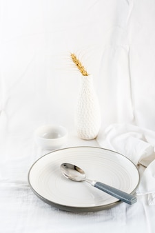Home serveerschalen om te eten. leeg bord en lepel op de tafel op een witte doek. verticale weergave