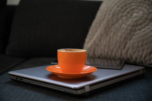 Home stilleven setting - oranje kopje koffie en digitale tablet geplaatst op laptop computer zittend op een bank.