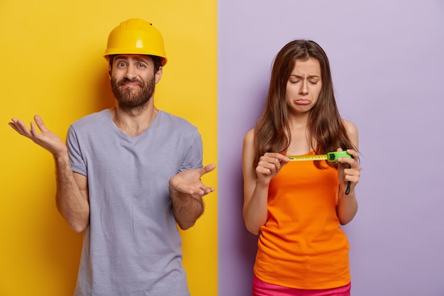 Home verbetering concept. ontevreden bedroefd vrouw kijkt naar meetlint, helpt man met renovatie van huis, aarzelende man staat verward, spreidt palmen, draagt gele veiligheidshelm, paars t-shirt