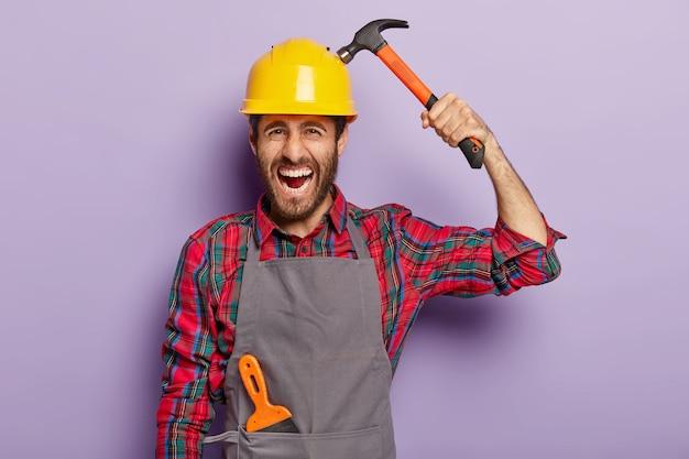 Home verbetering, reparatie, bouwen en repareren concept. geërgerd voorman draagt helm en houdt hamer vast, bezig met werken in werkplaats, schreeuwt negatief. ervaren mannelijke ingenieur gebruikt bouwgereedschap