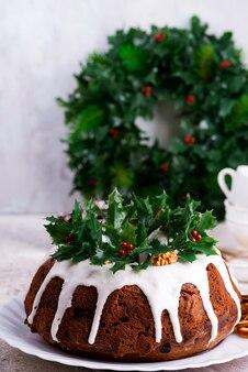 Homebaked donkere chocolade bundt cake van kerstmis die met hulstbessentakken wordt verfraaid op steen