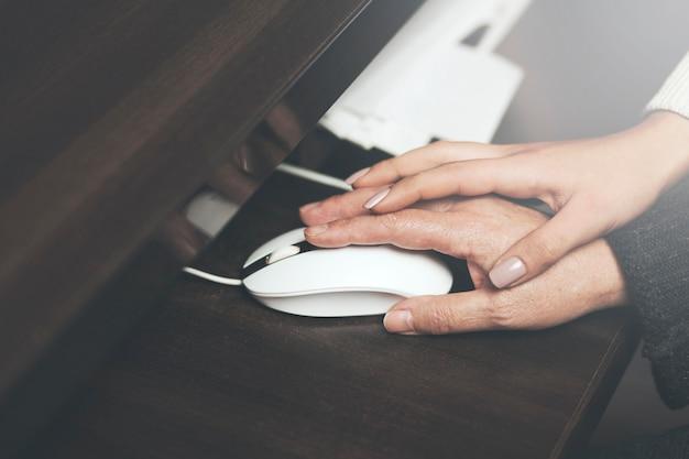 Homecarer met oudere vrouw met behulp van laptopcomputer