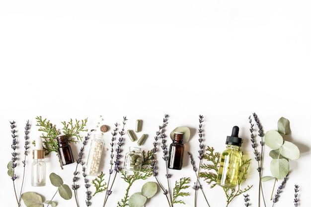 Homeopathie eco alternatieve geneeskunde concept - klassieke homeopathie pillen, thuja, eucalyptus, essentiële lavendel en aroma-olie en helende kruiden en op witte muur. flatlay. bovenaanzicht. copyspace